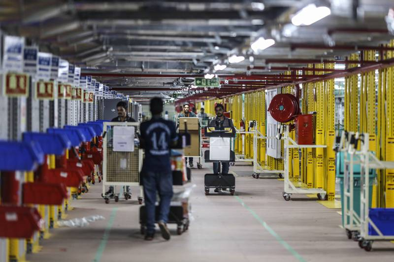 Employees push carts through Amazon.com Inc.'s fulfillment center in Hyderabad, India on Thursday, Sept. 7, 2017. Amazon opened its largest Indian fulfillment center in Hyderabad. The center spans 400,000 square feet with 2.1m cubic feet of storage capacity the company said in a statement. Photographer: Dhiraj Singh/Bloomberg via Getty Images