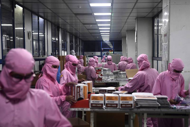 In this photograph taken on September 2, 2020, workers pack syringes at the Hindustan Syringes factory in Faridabad. - India's biggest syringe manufacturer is ramping up its production to churn out a billion units, anticipating a surge in demand as the global race to find a COVID-19 coronavirus vaccine heats up. (Photo by SAJJAD HUSSAIN / AFP)
