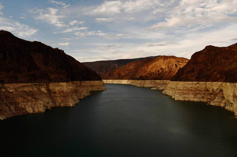 """(FILES) In this file photo taken on July 19, 2021 a """"bathtub ring"""" is visible at sunset during low water levels the Lake Mead reservoir due to the western drought  as seen from the Hoover Dam on the Colorado River at the Nevada and Arizona state border. - A huge reservoir that supplies water to tens of millions of people in the Western US is at such low levels that populations it feeds must reduce their useage next year, the government said August 16. A chronic drought has left huge swathes of the country parched, as man-made climate change forces shifts in the pattern of rainfall. That has left Lake Mead, the largest aritifical reservoir in the United States, which is fed by the mighty Colorado River, worryingly low -- at just a third of its capacity. (Photo by Patrick T. FALLON / AFP)"""