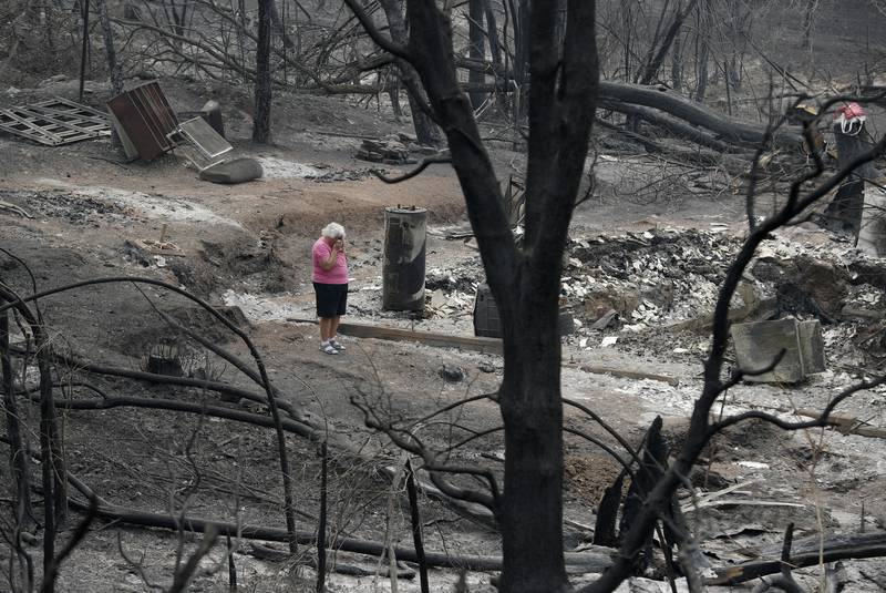 Aug. 9, 2018: Loretta Root wipes her eyes while visiting the remains of her home in the Keswick area burned in the Carr Fire in Redding, Calif. While California officials quickly determined an arsonist started the wildfire burning southeast of Los Angeles and that sparks from a vehicle produced the deadly wildfire in the city of Redding, causes for many of the state's worst blazes in the past decade remain a mystery.